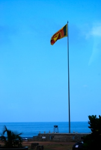 Sri Lankan flag with colors representing various ethnic groups.  The backdrop is the Indian ocean. ©Jean Janssen