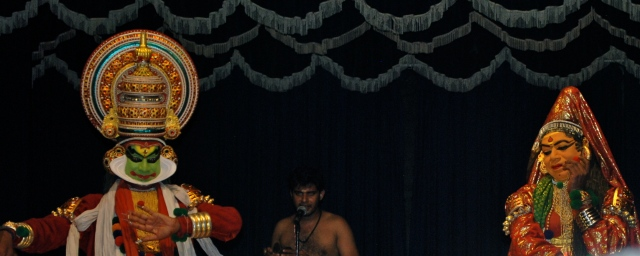 "Kathakali performance, traditional Buddhist ritual, Kochi, India.  The chanter appears in the middle of the two ""actors"". ©Jean Janssen"
