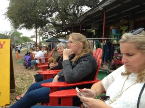 People watching at the Campbell Building in Warrenton, Texas.  (left to right) Beth Brown-holding Queen of Heirs mascot Peaches-Maggie studying the crowd and Emma texting.@Jean Janssen