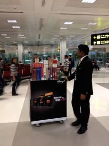 This gentleman rolls his duty free cart around the Doha International Airport selling cartons of cigarettes. ©Jean Janssen