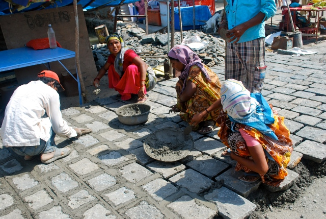 Building the sidewalk for us as we arrive.  Beside these women were the men chiseling the stone into bricks.  Elephanta Island, India ©Jean Janssen