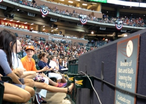 Craig Biggio is in white at the far end of our row.  Note the banners for Memorial Day and the warning sign for those seated in the first row. ©Jean Janssen