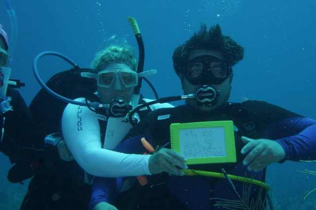 Rocky reached 100 dives on our trip to Belize.  He is now also a master diver.  Natasha the proud mom holding the slate. ©Bill Fuqua