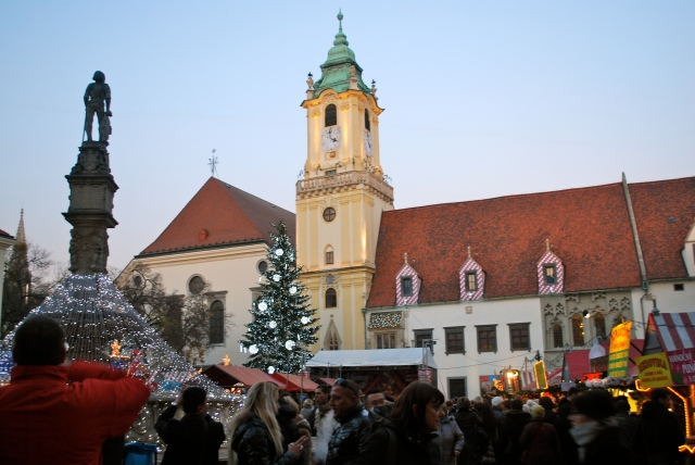 The clock tower is flanked by the large Christmas tree.  Light strands radiate from the fountain.  The Christmas market in the old city of Bratislava, Slovakia. ©Jean Janssen