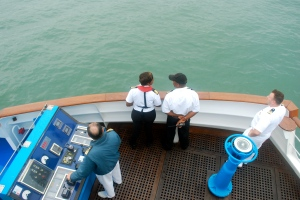 Officers on the Silver Wind Navigational Bridge which hangs out over each side of the ship to assist with docking.  Our captain is at the the controls, our pilot is in white, and the two other officers are the port pilots for East Durban. ©Jean Janssen