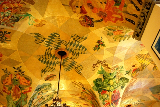 """The Hofbrauhaus is perhaps the most famous beer garden in Munich.  It upper hall was a popular meeting and rally location for the Nazis.  Although rebuilt, the upper floor was damaged by bombs during WWII.  The lower hall was undamaged.  Its beautiful painted ceiling features a child's pinwheel using the color of the Bavarian flag.  Formerly, the pinwheel was a swastika.  The ceiling is protected for it historical significance.  Because it can not be repainted, artists cleverly """"stored"""" the swastika to look like a pinwheel.  If yo look closely, you can see where the paint is darker and the original design exists. ©Jean Janssen"""