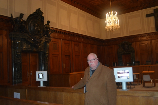 Boris in the courtroom at the Palace of Justice site of the Nuremberg Trials.  The defendants block is against the wall with the elevator control and doors visible against that wall. ©Jean Janssen