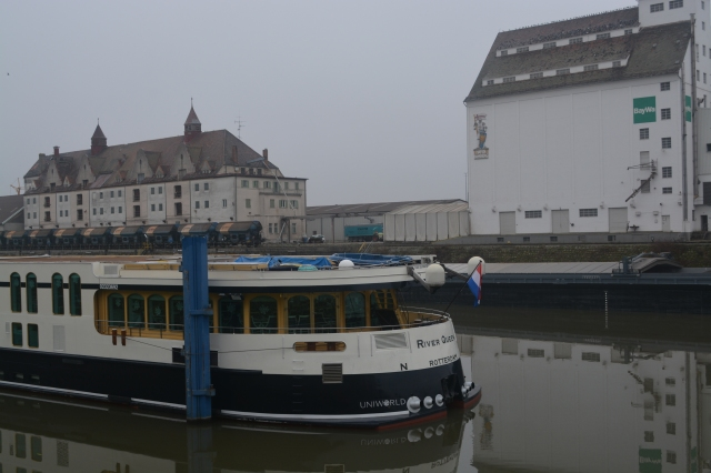 Our river cruise ship, Uniworld's River Queen on the industrial canal outside Bamberg, Germany.  Note the knight logo on the storage building. ©Jean Janssen
