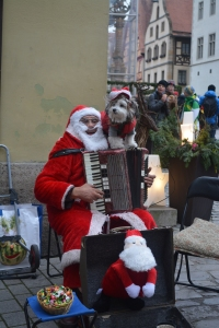 Santa busker, Rothenburg, Germany.  Santa's dog is real and walked around on his shoulder while he played and sang Christmas carols. ©Jean Janssen