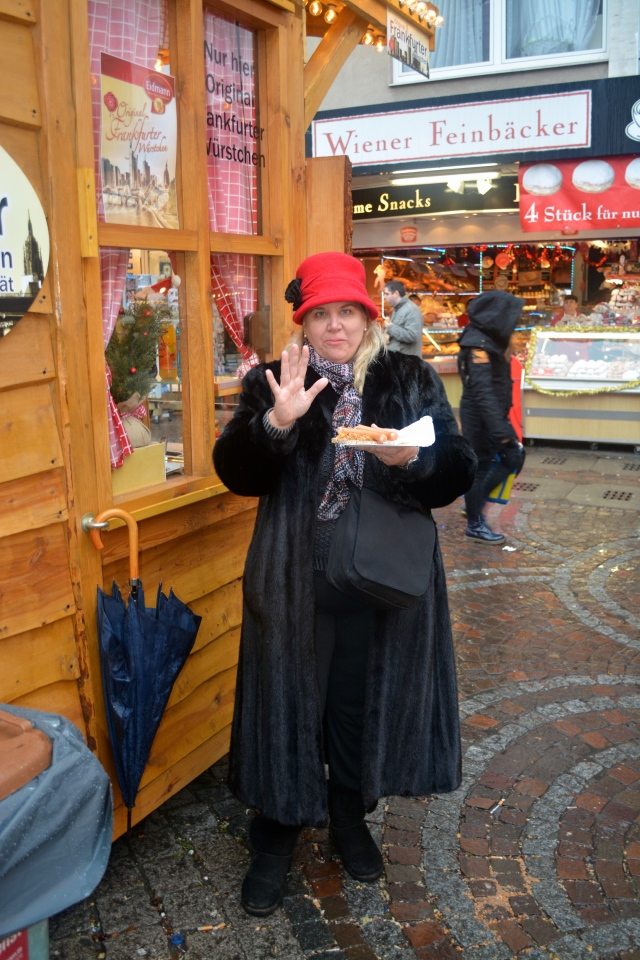 Natasha and her frankfurter in Frankfurt.  The red hat is the one I bought in Rothenburg. ©Jean Janssen