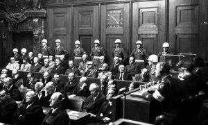 Photograph of the Nuremberg Trial defendants guarded by military police.