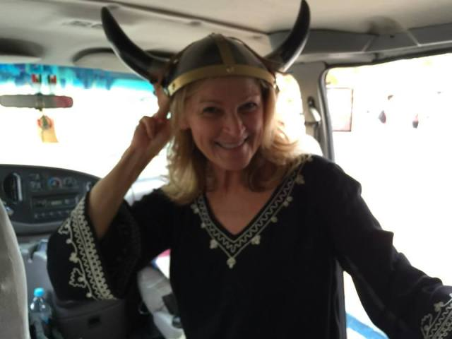Marne models one of Boris' big purchases, a viking helmet made of metal and cow horns, in the cab on the way back to Villa Descanso