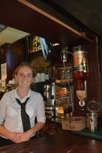 Our friendly barmaid Blaithin at the Abbey Tavern in Howth Ireland gave us a turn behind the bar and posed for us next to the large bottle of Powers Irish Whiskey used when making the Irish coffees. Blaithin grew up nearby.  ©Jean Janssen